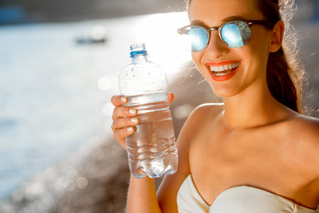 reflaction: Young woman drinking sparkling water from transparent bottle on the beach on sunset Stock Photo