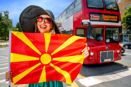 macedonian flag: Woman with macedonian flag in Skopje city with red routemaster bus on background. Promoting tourism in Macedonia