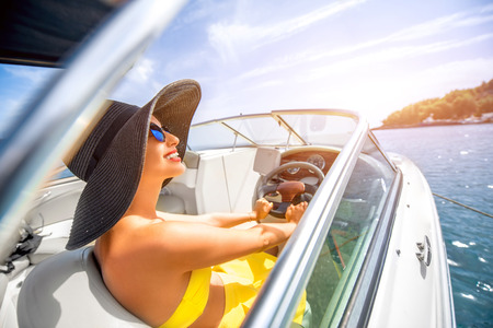 people: Young and pretty woman in yellow skirt and swimsuit with hat and sunglasses driving luxury yacht in the sea.