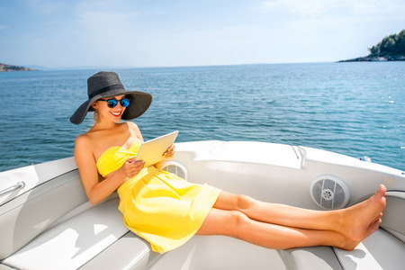 Young woman in yellow swimsuit and skirt reading with digital tablet on the yacht floating in the sea