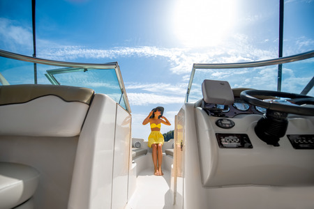 Young and pretty woman in yellow swimsuit relaxing on the yacht floating in the sea. Luxury summer recreation concept