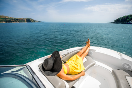 recreation yachts: Young and pretty woman in yellow swimsuit with big hat relaxing on the yacht floating in the sea. Luxury summer recreation