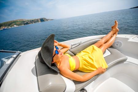 donna ricca: Giovane e bella donna in costume da bagno giallo con grande cappello di relax in barca che galleggia nel mare. Ricreazione estate di lusso