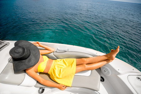 yacht people: Young and pretty woman in yellow swimsuit with big hat relaxing on the yacht floating in the sea. Luxury summer recreation