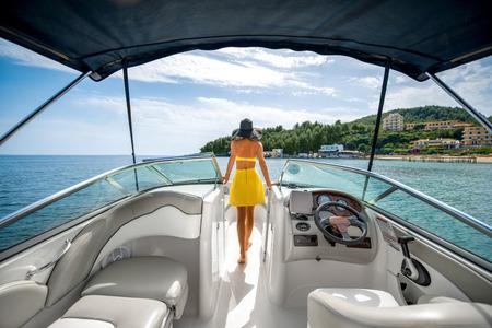 donna ricca: Giovane e bella donna in costume da bagno giallo in piedi sulla barca che galleggia nel mare con vista sull'isola