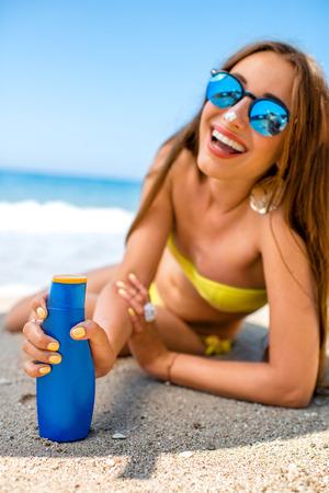 해변에서 선탠 크림 병을 게재하는 여자.
