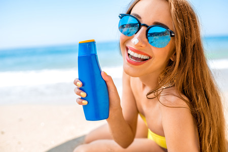 Femme montrant une bouteille de crème de bronzage sur la plage. Banque d'images