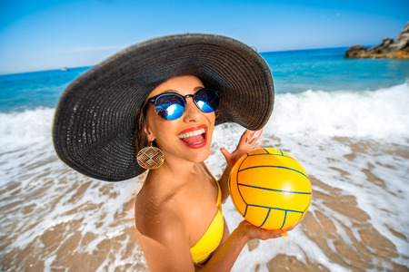 sexy funny: Playful woman in big hat with the yellow ball standing on the beach. Stock Photo
