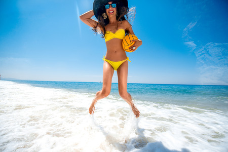 Playful woman in yellow swimsuit jumping with the ball splashing water in the sea.