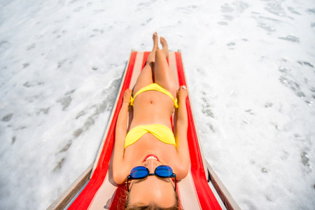 sunbath: Young and beautiful woman relaxing and having sunbath on the red sunbed in the sea. Top view with wide angle Stock Photo