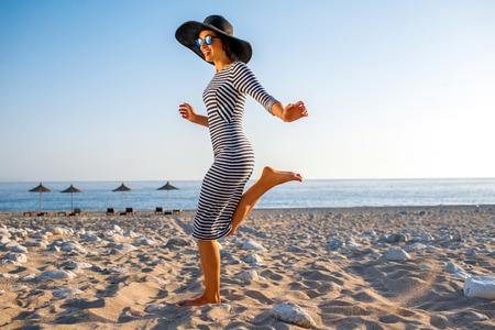 Jonge en elegante vrouw in gestripte kleding met een hoed springen op het strand op zonsondergang