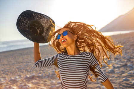Young and happy woman in stripped dress jumping with a hat in the hand on the beach on sunset against the sun. Feeling free and joyful Stock Photo