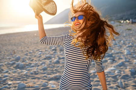 Young and happy woman in stripped dress jumping with a hat in the hand on the beach on sunset against the sun. Feeling free and joyful 스톡 콘텐츠