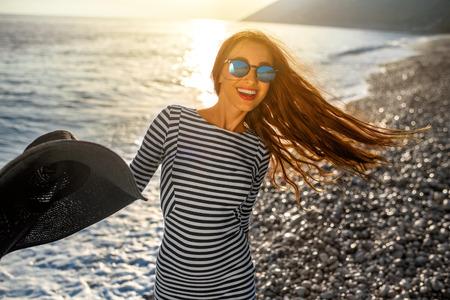Jong en gelukkige vrouw in gestripte jurk springen met een hoed in de hand op het strand op zonsondergang tegen de zon. Gevoel vrij en blij