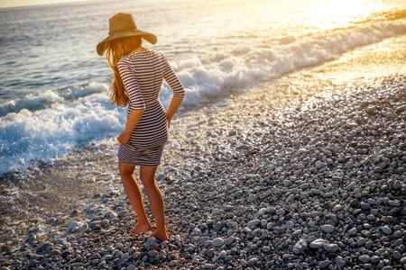 Jonge en elegante vrouw in gestripte kleding met een hoed lopen naar de zee op het strand op zonsondergang