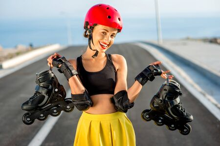 Sport woman in red helmet holding black rollers standing on the asphalt road with blue water and sky background