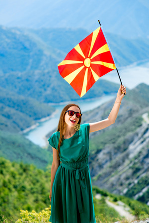 macedonian flag: Young happy woman in green dress holding macedonian flag on the top of mountain near Kozjak lake in Macedonia. Promoting tourism in Macedonia