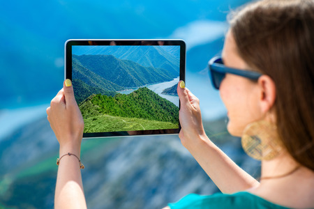Young woman photographing beautiful landscape with digital tablet standing on the top of mountain