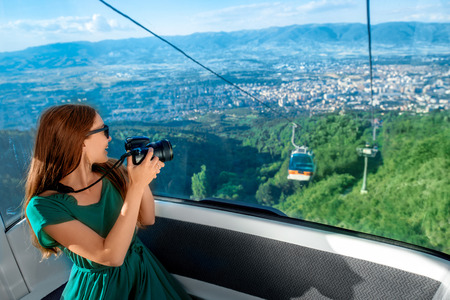 Young woman tourist photographing beautiful cityscape sitting in cable car on the way to the top of Vodno mountain near Skopje city in Macedonia Stock Photo