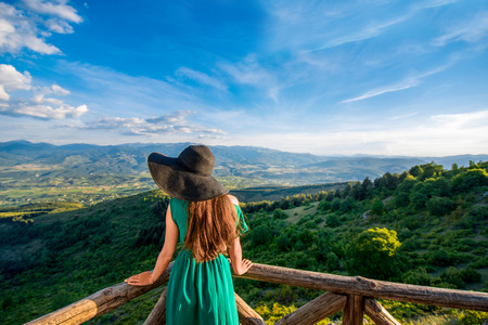 blue back: Woman standing on the big terrace with beautiful mountain landscape view in Macedonia