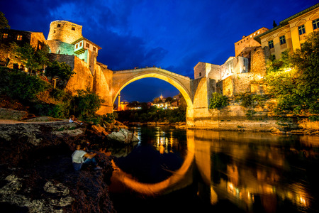 Beautiful night view on Mostar city with old bridge and ancient buildings on Neretva river in Bosnia and Herzegovina