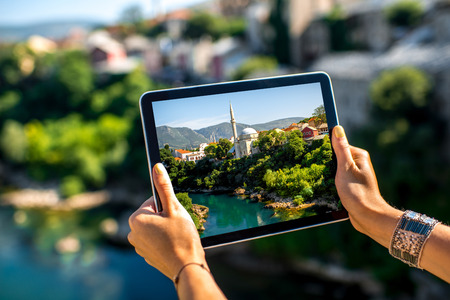 Woman photographing with digital tablet Mostar city in Bosnia and Herzegovina. Close up view focused on hands with tablet Stock Photo