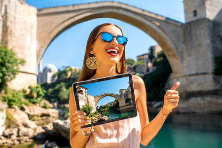 promoting: Woman showing tablet with photo of Mostar city. Promoting tourism in Bosnia and Herzegovina