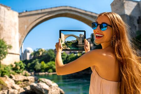female clothing: Female tourist photographing with digital tablet old bridge in Mostar city in Bosnia and Herzegovina. Stock Photo