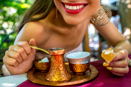 cezve: Woman smile with turkish coffee in traditional bronze cezve  in the restaurant Stock Photo