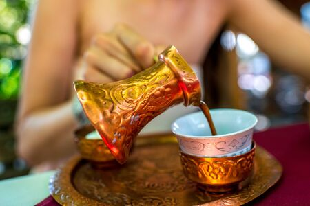 cezve: Woman pouring turkish coffee from traditional bronze cezve  in the restaurant Stock Photo