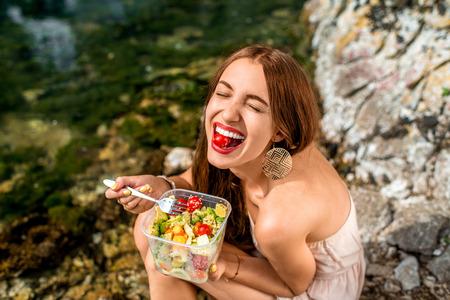 eten: Vrouw die gezonde salade van plastic container in de buurt van de rivier