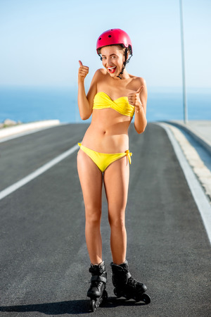 women body: Beautiful woman in yellow swimsuit and red helmet skating on rollers on the asphalt road near the sea in summer Stock Photo