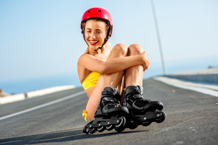 hot rollers: Beautiful woman in yellow swimsuit and red helmet skating on rollers on the asphalt road near the sea in summer Stock Photo