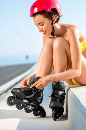 hot rollers: Beautiful woman in yellow swimsuit and red helmet lacing up rollers sitting on the road near the sea in summer Stock Photo