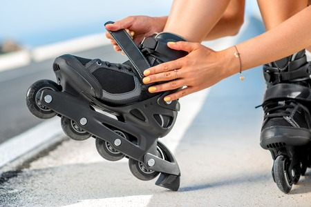 hot rollers: Woman lacing up rollers on the asphalt road near the sea in summer. Close up view focused on hands and rollers Stock Photo