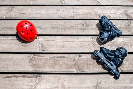 casco rojo: Patinaje rodillos y casco rojo en las tablas de madera. Vista superior con espacio para el texto