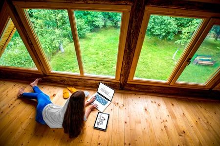 Femme en jeans et chemise blanche gisant sur le sol avec un ordinateur portable et une tablette près de la fenêtre avec vue sur le jardin dans un chalet en bois confortable.