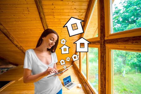 projecting: Young and cute woman designing or projecting a house with digital tablet standing near the window in cozy wooden cottage.