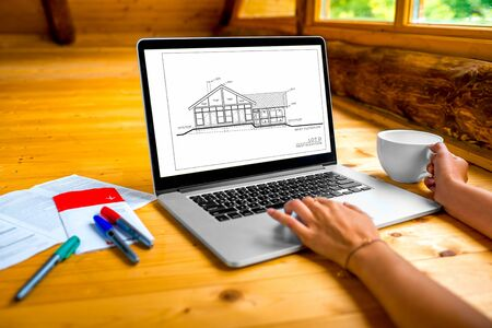 projecting: Architects projecting stuff, laptop with drawing, markers and coffe cup on the wooden floor in the cottage Stock Photo