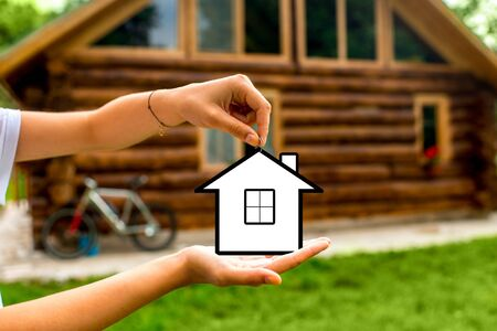 sold small: Female hands holding small house icon with wooden cottage on background. The concept of countryside estate