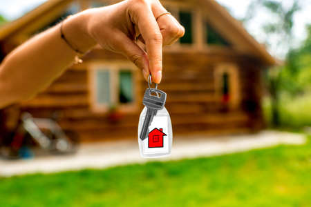 sold small: Female hands holding house key with wooden cottage on background. The concept of buying countryside estate Stock Photo