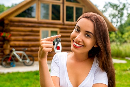sold small: Happy owner holding keys from the wooden small cottage. Buying property concept