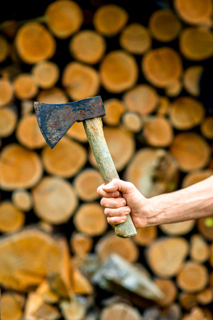 hatchet man: Male hand holding an ax on a stack of firewood background Stock Photo