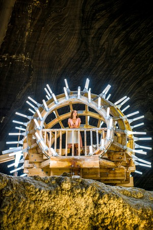 turda: TURDA, ROMANIA - JUNE 30 2015: Young female tourist at illuminated instalation in the Salt Mine Salina Turda museum in Romania Editorial