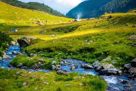 Mooie mening over bergrivier met plattelandshuisje op Fagaras-bergen in Roemenië Stockfoto