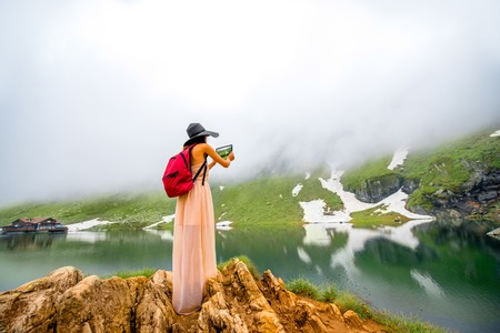 balea: Female traveler in long dress and big hat with red backpack photographing mountain lake with fog and snow. Traveling in Romania