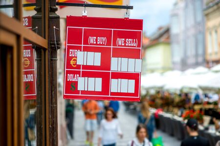 fil: Exchange rate table with empty slots to fil in on the crowded street