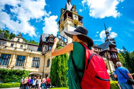 back pack: Female tourist in green dress, big hat and back pack photographing with digital tablet Peles castle in Romania. Back view