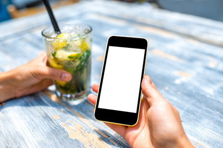 mohito: Female hand using a phone with isolated screen on wooden vintage table holding a glass with mohito