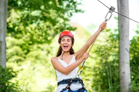 casco rojo: Mujer joven y bonita en montar casco rojo en una tirolesa en el bosque. Activo tipo de deportes de recreación